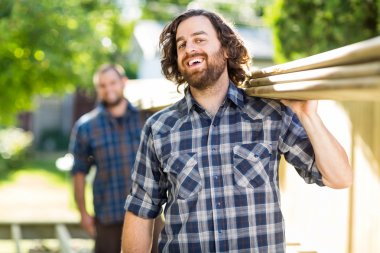 Carpenter With Coworker Carrying Planks While Laughing