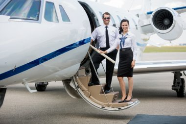 Airhostess And Pilot Standing On Private Jets Ladder