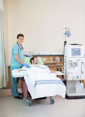 Portrait Of Nurse Standing By Patient Receiving Dialysis