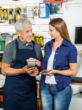 Female Customer Paying Through Smartphone In Hardware Store