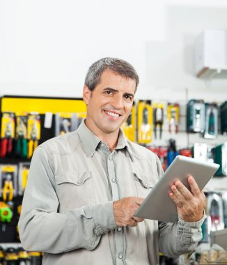 Confident Man Using Tablet Computer In Hardware Store