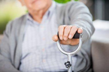 Midsection Of Senior Man Holding Walking Stick