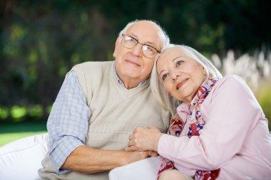 Loving Senior Couple Sitting On Chairs