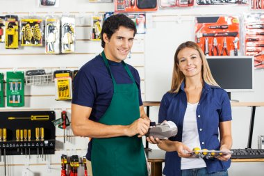 Woman Holding Screwdriver Set With Worker Swiping Credit Card