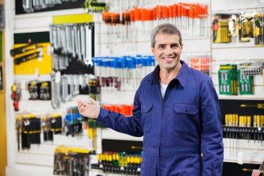 Worker In Overalls Gesturing In Hardware Store