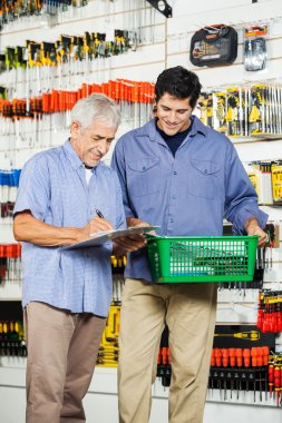 Father And Son Buying Tools In Hardware Store