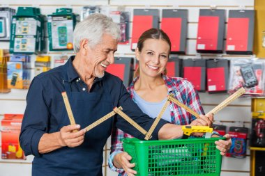 Customer With Worker Holding Folding Ruler In Hardware Shop