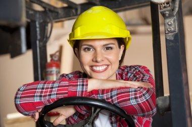 Happy Engineer Leaning On Forklifts Steering Wheel