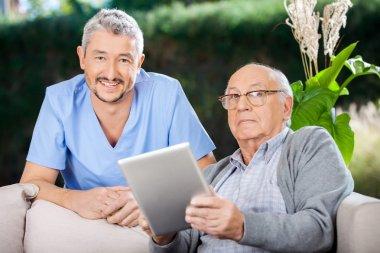 Male Caretaker And Senior Man Holding Digital Tablet