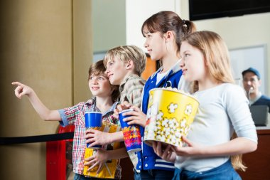 Boy Showing Something To Siblings At Box Office
