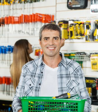 Man Carrying Basket Full Of Tools In Store