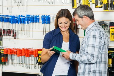 Couple Analyzing Product In Hardware Store