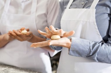 Female Chefs Making Pasta Dough Balls In Kitchen