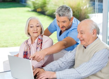 Male Caretaker Assisting Senior Couple In Using Laptop