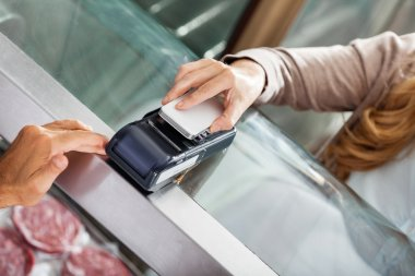 Customer Making Payment Through Smartphone In Butchery