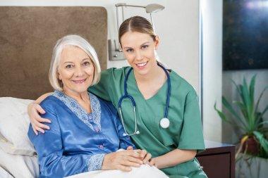 Happy Caretaker With Arm Around Senior Woman At Nursing Home