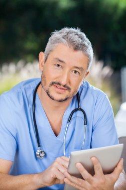 Male Nurse Using Digital Tablet At Nursing Home
