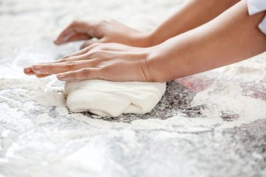 Female Chefs Hands Kneading Dough At Counter