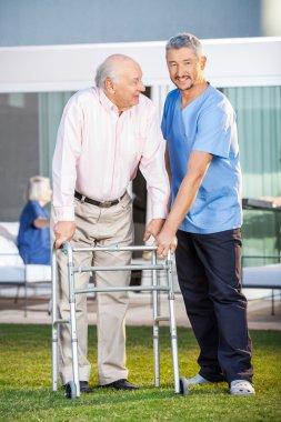 Smiling Caretaker Assisting Senior Man To Use Walking Frame