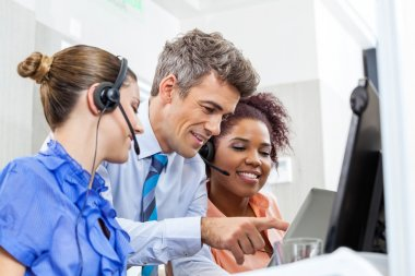 Manager With Customer Service Executives Using Tablet Computer