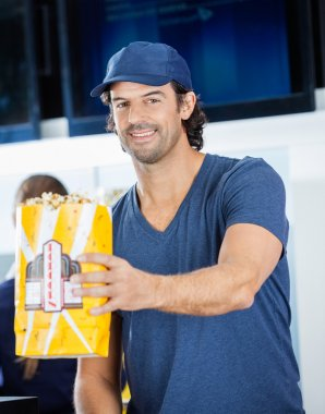 Smiling Male Worker Offering Popcorn At Concession Stand