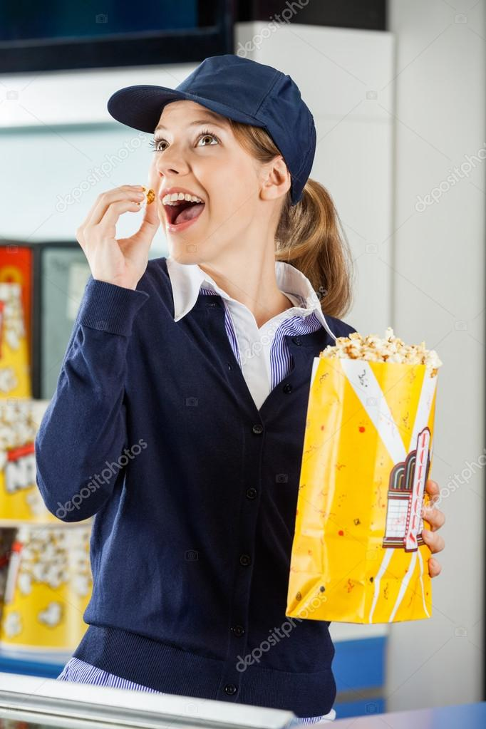 Happy Worker Eating Popcorn At Cinema Concession Stand — Stock Photo ...