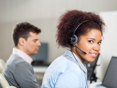 Customer Service Representative Wearing Headset At Office Desk