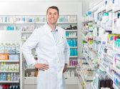 Mužské lékárník stojící s rukama v bok v lékárně