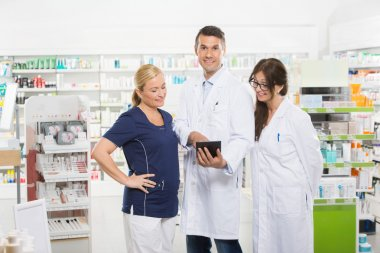 Confident Pharmacist Using Digital Tablet With Coworkers