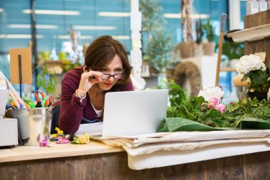 Florist Holding Glasses While Using Laptop In Flower Shop