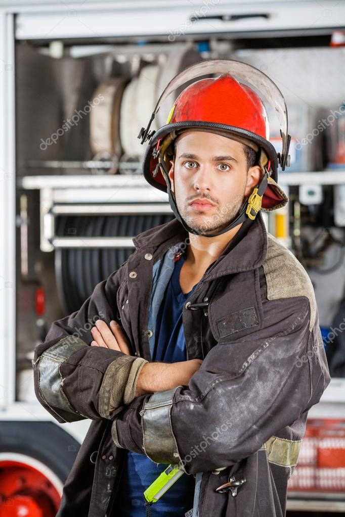 Confident Firefighter Standing Arms Crossed Against Firetruck