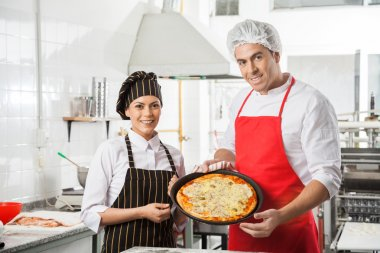 Happy Chefs Presenting Pizza At Commercial Kitchen