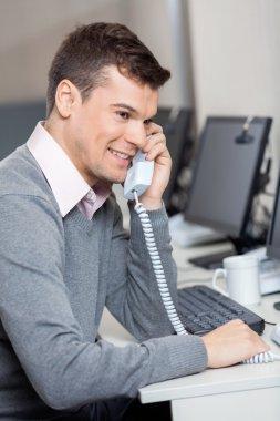 Customer Service Representative Using Landline Phone At Desk