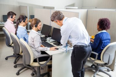 Manager Assisting Customer Service Agent In Call Center