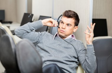 Angry Customer Service Representative Gesturing While Using Head