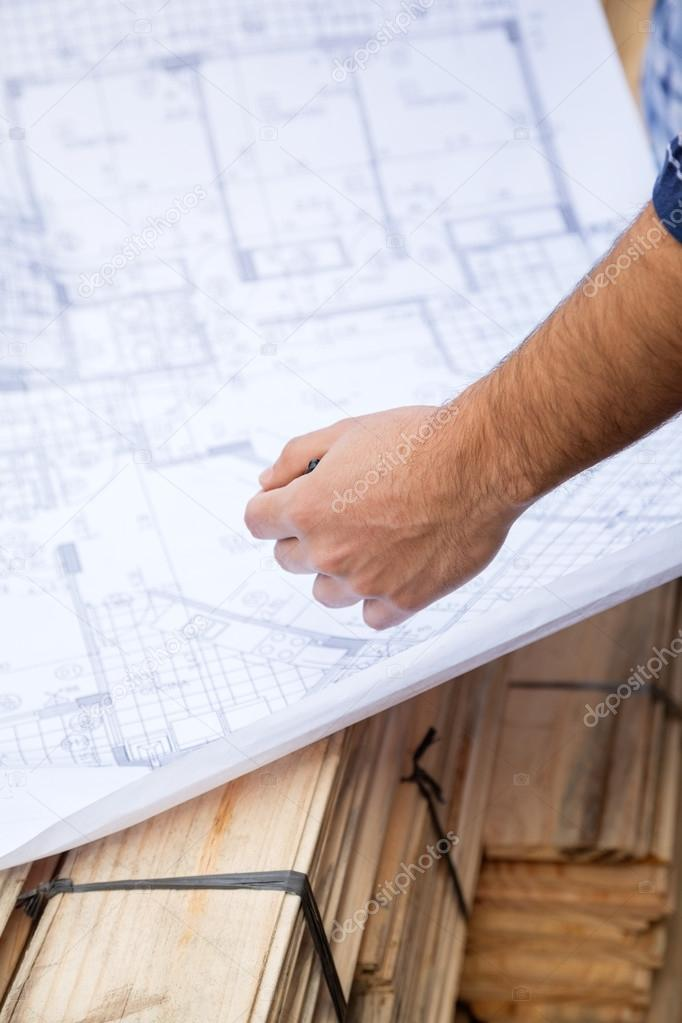 Carpenter With Blueprint At Site