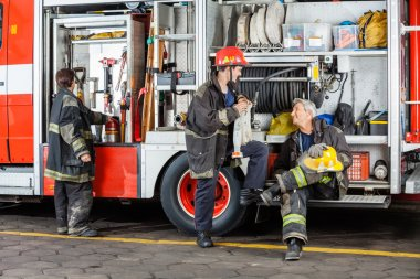 Firefighters Discussing By Truck