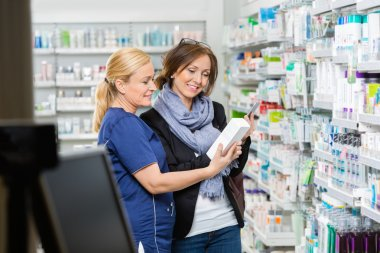 Chemist Showing Product To Customer Holding Cell Phone In Pharma