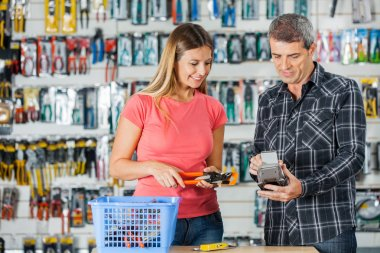 Couple Paying For Pliers Through Smartphone In Store