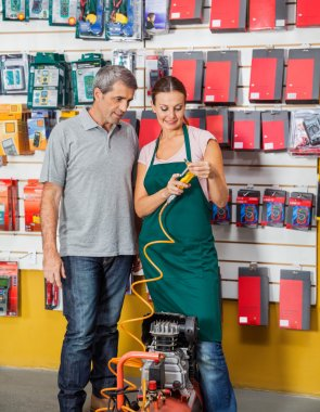 Saleswoman Explaining Air Compressor To Customer In Store