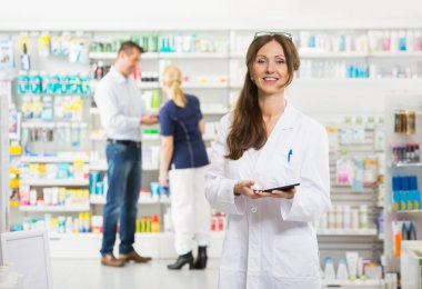Smiling Female Chemist Holding Digital Tablet At Pharmacy