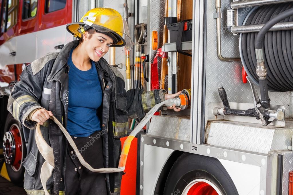 Portrait Of Happy Firefighter Adjusting Hose In Truck