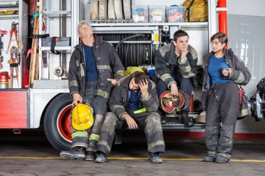 Team Of Tired Firefighters At Station