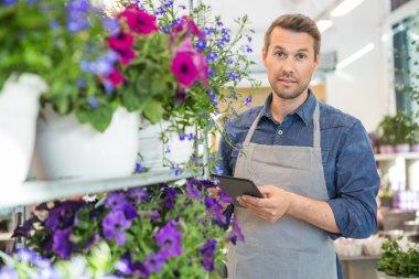 Confident Worker Using Digital Tablet In Flower Shop