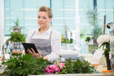 Florist Using Digital Tablet In Flower Shop