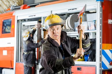 Confident Fireman Holding Axe At Fire Station