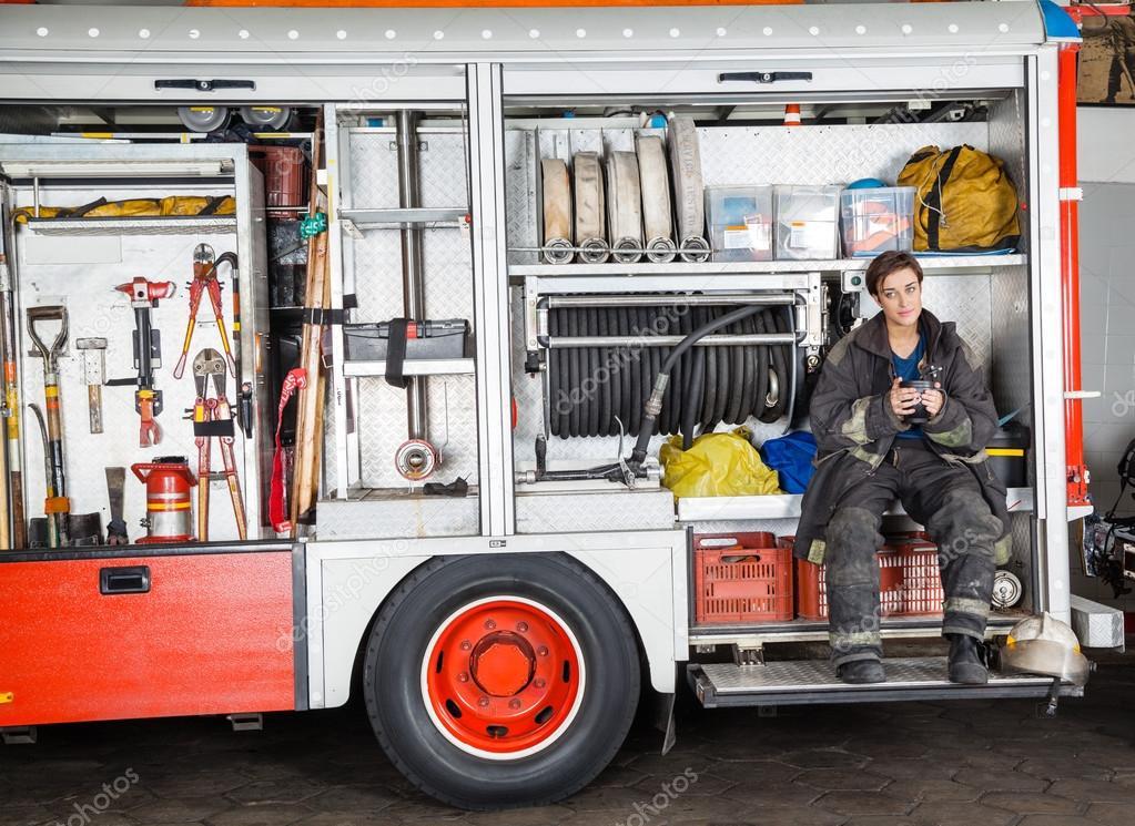 Firewoman Holding Coffee Mug In Truck