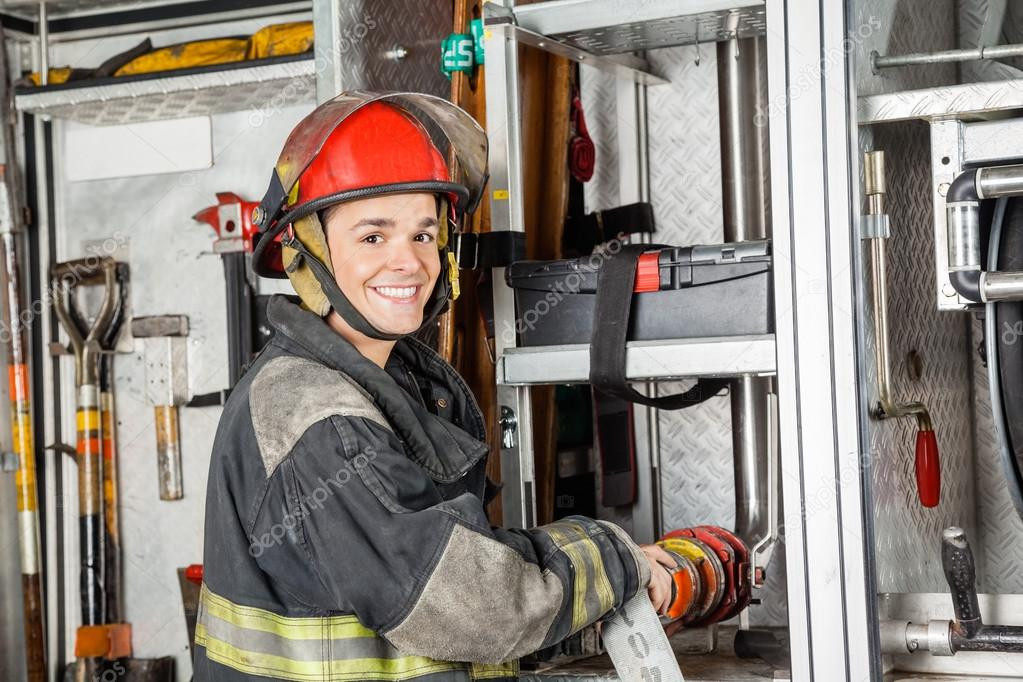 Happy Firefighter Fixing Water Hose In Truck