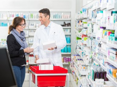 Male Pharmacist Showing Medicines To Female Customer