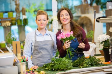 Florists Making Bouquet Of Roses In Shop